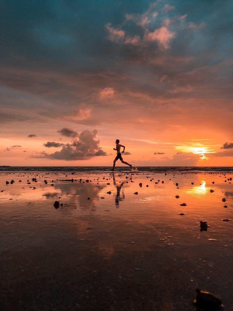 An athlete running along a beach at sunset