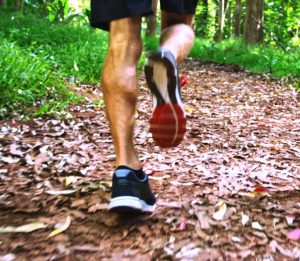 An athlete running along a path through trees