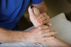 A podiatrist manipulating the foot of a patient with foot pain