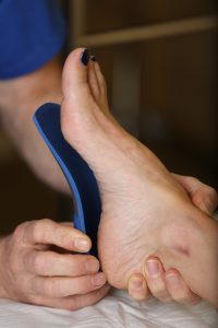 A sports podiatrist fitting a patient with orthotics