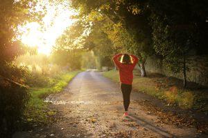 A jogger walking along a sunny country road