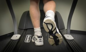 Sports podiatrist using a treadmill for gait analysis