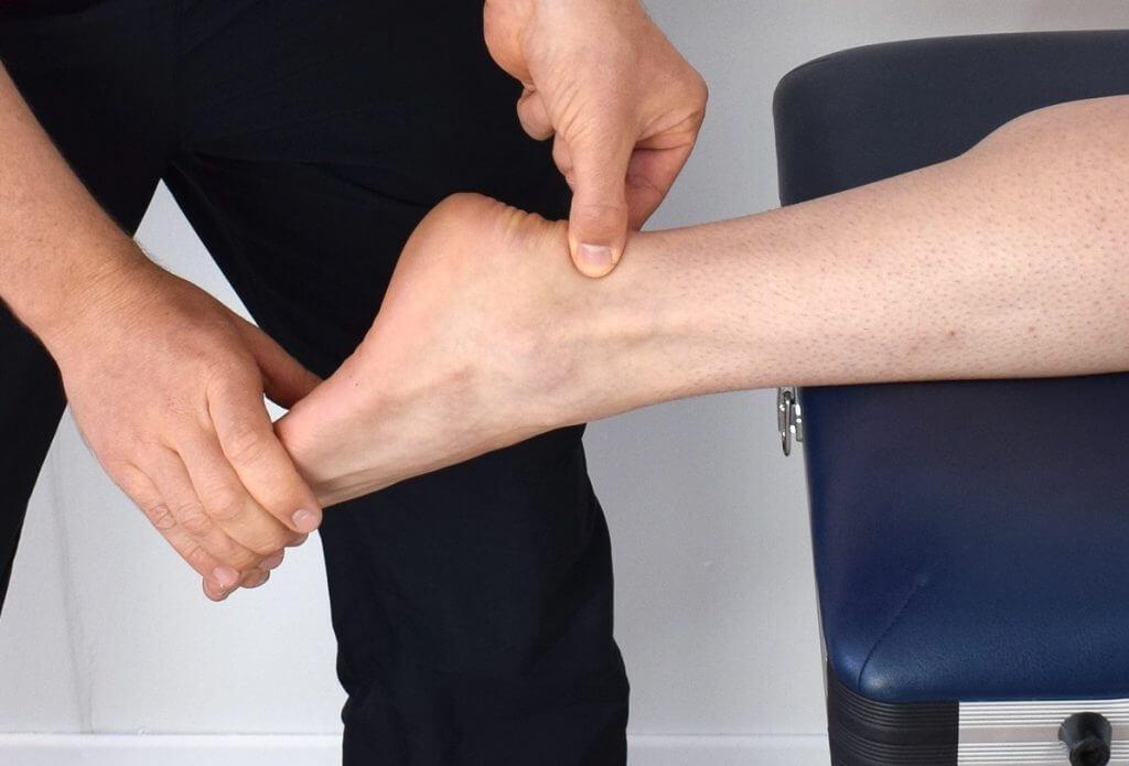 Podiatrist examining a patient's ankle