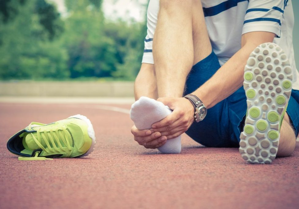 An athlete sitting on a running track suffering foot pain from overtraining
