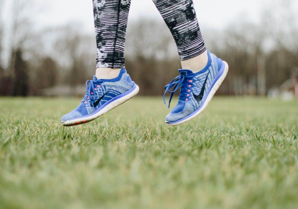 A runner jumping in a grassy field