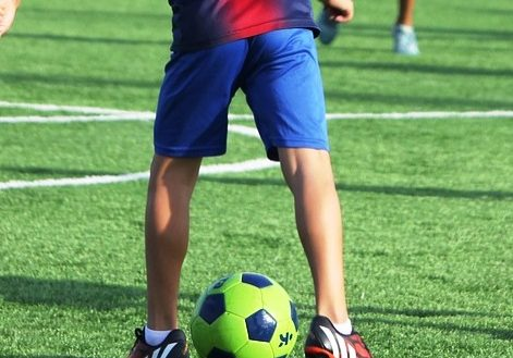 A child playing football on a grass pitch