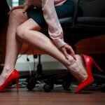A business woman at a desk suffering with heel pain