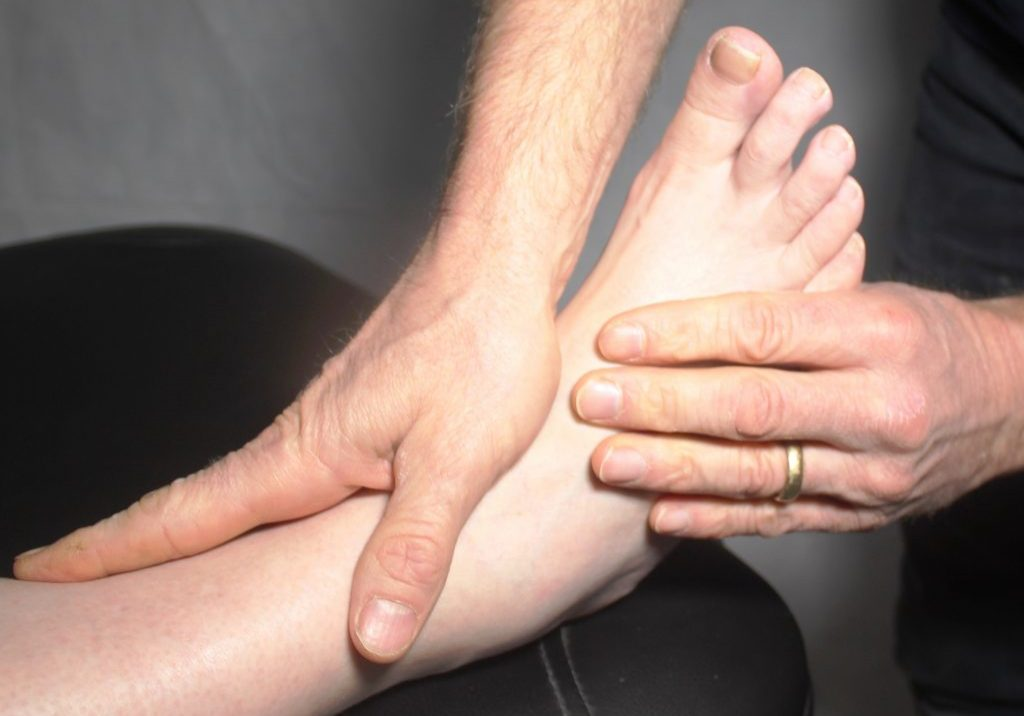 A podiatrist examining a patient's ankle